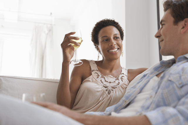 a woman sitting on a sofa holding a glass of wine while she talks to a man