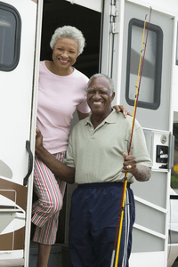 a senior couple on a fishing trip together stepping out of a van