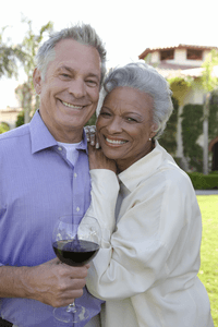 a mature couple smiling and enjoying a glass of wine outside