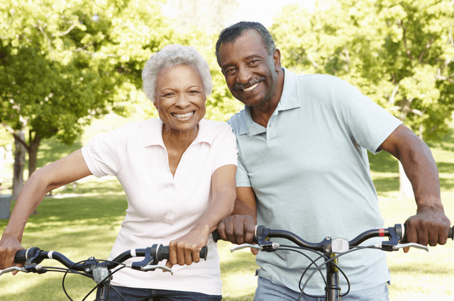 a mature black couple on bicycles